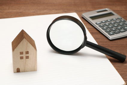 家の模型と虫メガネと電卓